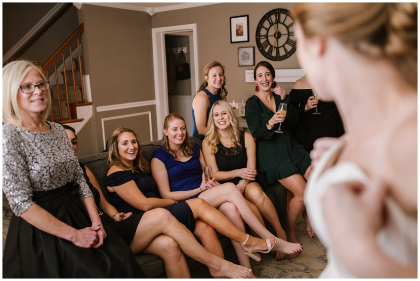bride getting in dress with bridesmaids